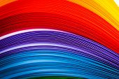 Rainbow colored quilling paper laid out in waves and shapes