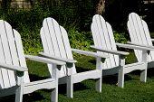 Row of white Adirondack chairs