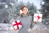 Young Beautiful Woman With Gift Boxes In Winter Forest