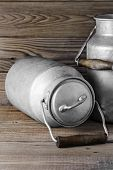 Aluminum old milk cans on a wooden background in the vertical format