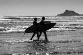 foto of watersports  - Silhouettes surfers at sunset on Oregon beach going back home USA  - JPG