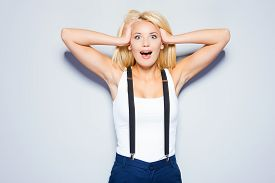 stock photo of suspenders  - Surprised young woman holding hands in hair and staring at camera while standing against grey background - JPG
