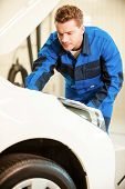 image of concentration man  - Concentrated young man in uniform examining car while standing in workshop  - JPG