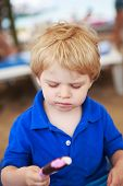 foto of strawberry blonde  - Little blond toddler eating chocolate and strawberry ice cream pop outdoors - JPG