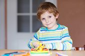 image of preschool  - Smiling preschool kid boy having fun with dough colorful modeling compound sitting at table at home or nursery - JPG