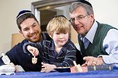 picture of dreidel  - Boy with father and grandfather spinning dreidel celebrating Hanukkah - JPG
