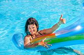 picture of mattress  - Happy woman  swimming on inflatable beach mattress and showing thumb up - JPG