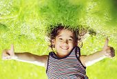 picture of upside  - Portraits of happy kid playing upside down outdoors in summer park with thumbs up - JPG