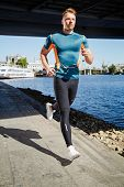 pic of leggins  - Young handsome man running along the embankment near the river under the bridge - JPG