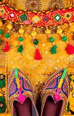 foto of flea  - Colorful ethnic shoes and gipsy belt on yellow Rajasthan cushion cover on flea market in India - JPG