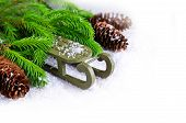 pic of sled  - Decorative sled on snow with fir tree branches on white background - JPG