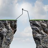 stock photo of cliffs  - Overcoming an obstacle concept as a businessman with very long legs walking past through two high cliffs as a success bridge metaphor to surmount an obstruction and solve a problem - JPG