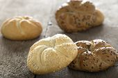 picture of bagel  - Close up of a sesame seed bagel and others with seeds over wooden background - JPG