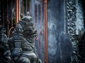 stock photo of immoral  - Gardian statue at the Bali temple entrance Indonesia - JPG