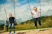 foto of swingset  - Little blonde boys having fun at the playground - JPG