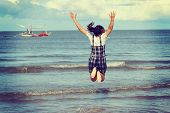 stock photo of jumping  - Jump to the freedom Asian woman jumping on the beach retro and vintage tone - JPG