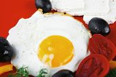 picture of scrambled eggs  - fried scrambled eggs eye with white goat feta cheese on red plate isolated over white background with black olives and vegetables - JPG