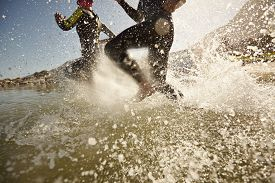 pic of triathlon  - Two triathlon participants running into the water for swim portion of race - JPG