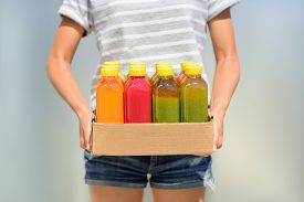 foto of cleanse  - Woman holding delivery box of freshly cold pressed fruit and vegetable juice bottles - JPG