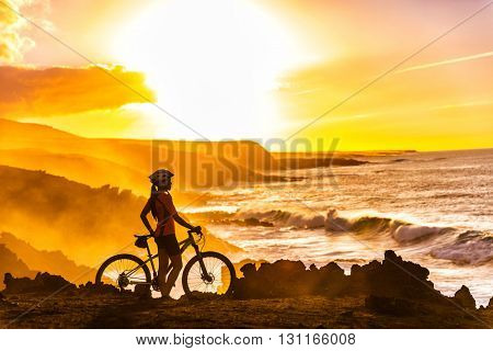 MTB cyclist mountain biking woman cycling looking at view on bike trail on coast at sunset. Person o