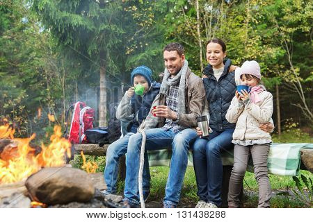camping, travel, tourism, hike and people concept - happy family sitting on bench and drinking hot t