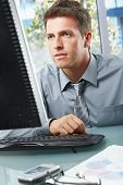 Elegant professional businessman working on computer looking at screen with hand on mouse in sunlit