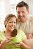 Portrait of smiling couple at home, woman holding tea cup in hands.