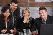 Happy young businesspeople at meeting table in corporate office, looking at camera, smiling.