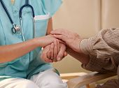 Closeup of joined hands of nurse and elderly patient.