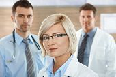 stock photo of medical staff  - Medical team on hospital corridor female doctor in front looking at camera - JPG