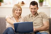 stock photo of computer-screen  - Smiling couple sitting together browsing internet on laptop computer - JPG