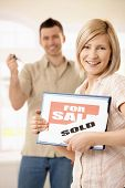 Happy woman holding for sale sign, laughing man in background holding keys of new house.?