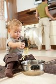 Little boy sitting on carpet in kitchen playing with cooking pots, mother preparing food in backgrou