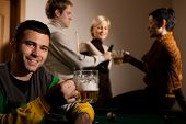 Portrait of smiling young man drinking beer at snooker table, friends having drink in background.?