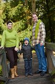 pic of nuclear family  - Young happy family of three standing in park on bridge - JPG