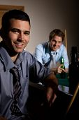Portrait of two men at snooker table, having beer, smiling.?