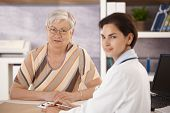 image of doctors office  - Female pensioner at doctors office looking at camera - JPG