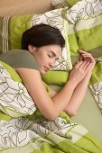 Mid-adult woman smiling in sleep in colorful bedclothes.?