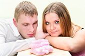 Pregnant Woman With Her Husband Looking At Baby`s Booties