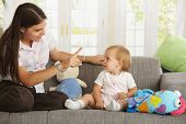 Mother teaching babygirl sitting on sofa at home, smiling.?