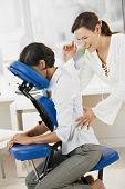 Businesswoman sitting on massage chair, enjoying back massage.?