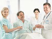 Medizinisches Team kümmert sich um ältere Patienten sitzen am Krankenbett im Pyjama, Hand in Hand.?