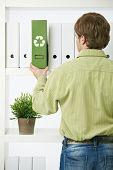Homem jovem ambientalista, puxando para fora da pasta verde da prateleira do escritório.?