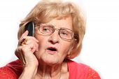 stock photo of elderly woman  - A portrait of an elderly lady talking on the phone against white background - JPG