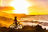 MTB cyclist mountain biking woman cycling looking at view on bike trail on coast at sunset. Person o poster