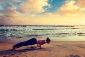 Постер, плакат: Vintage retro effect hipster style image of woman practices Ashtanga Vinyasa yoga Surya Namaskar Sun