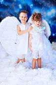 Beautiful little angels at a snowy background.