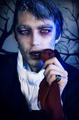 Portrait of a handsome young man with vampire style make-up. Shot in a studio.