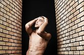 stock photo of skinheads  - Portrait of a handsome muscular man posing over black background and brick wall - JPG