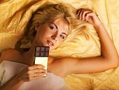 Beautiful girl with a chocolate craving lying on luxury golden fabric